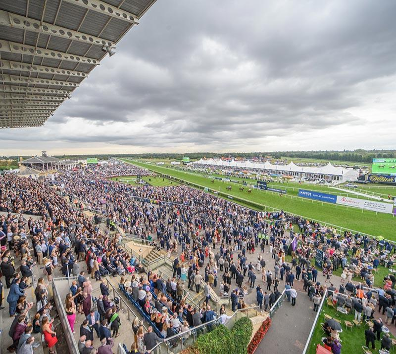 A view from a high vantage point in the grandstand of a large crowd at Doncaster Racecourse.