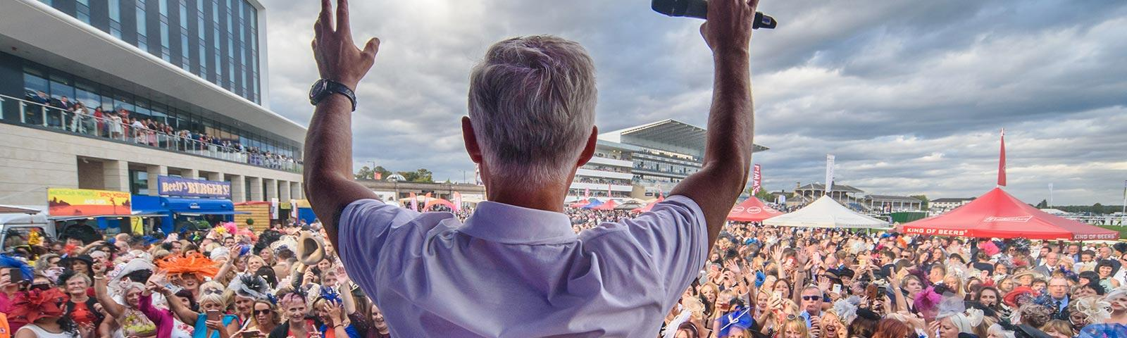 DJ facing a concert crowd at Doncaster Racecourse