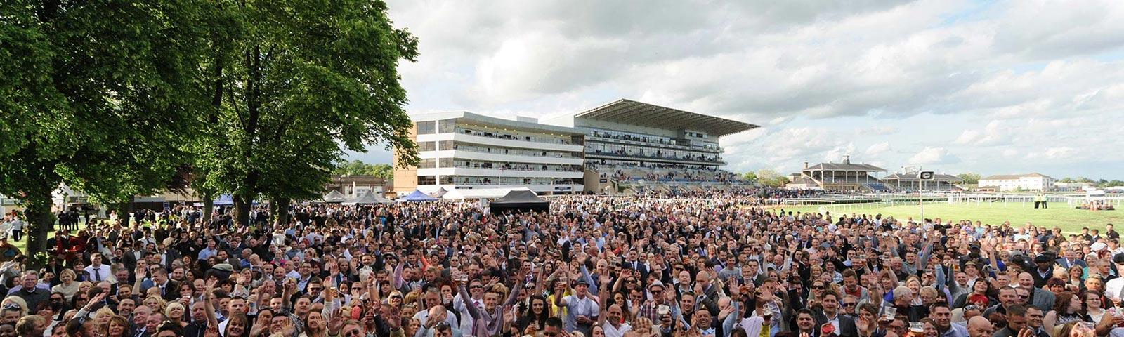 A large crowd at Doncaster Racecourse with the Grandstand and Hilton Garden Inn Hotel visible in the background.