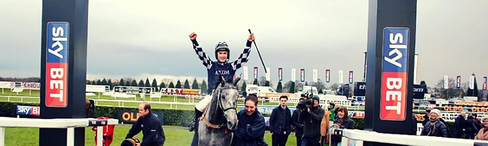 A winning jockey raising his hands at the end of a race at Doncaster Racecourse