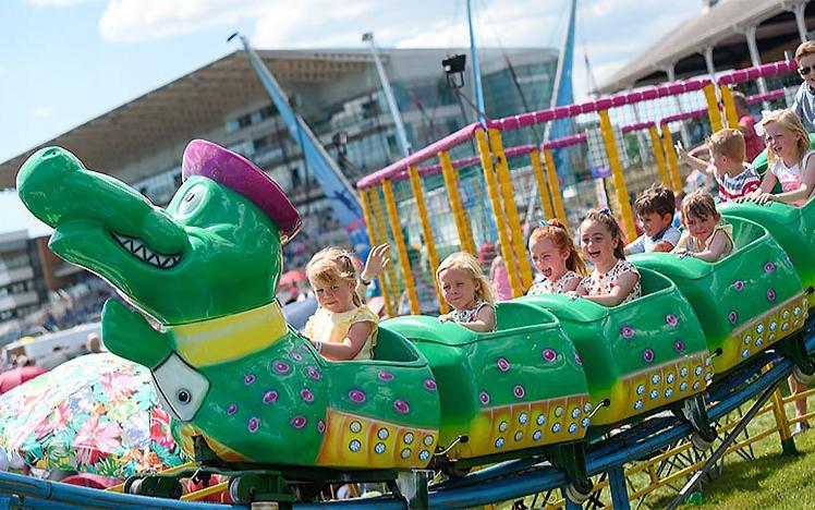 Children scream on the back of a rollarcoaster in the shape of a caterpillar
