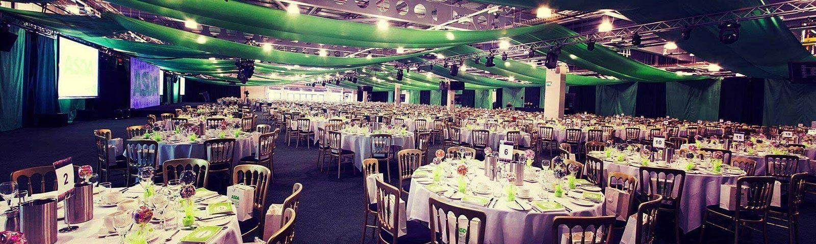 A large hall with a large amount of tables all prepared for exhibition guests.